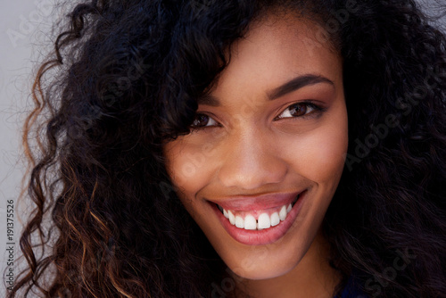 Fototapety, obrazy: Close up smiling young african american woman against gray wall