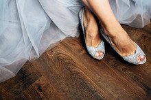 Bride's Legs In Chick Silver Shoes On Wooden Floor
