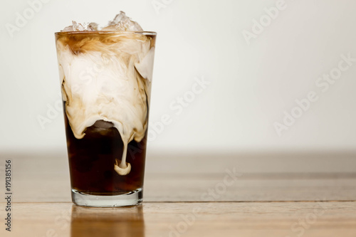 Photo  Iced coffee on a wood table with cream being poured into it showing the refreshi