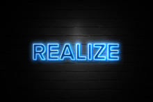 Realize Neon Sign On Brickwall