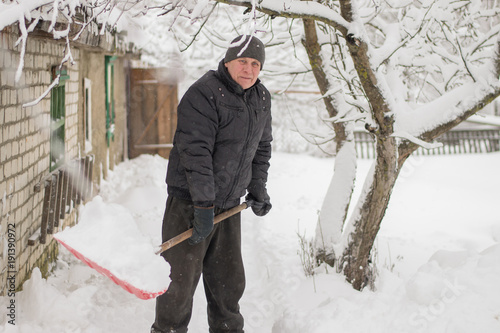 a funny elderly man with a gray head and toothless cleans snow with a plastic sh Wallpaper Mural