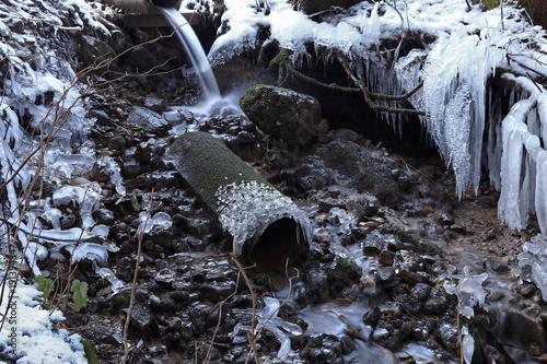Fotografie, Obraz  Langzeitbelichtung von einem Bach mit vielen Eiszapfen