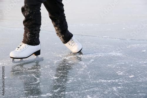 Fotobehang Wintersporten Young woman ice skating outdoors