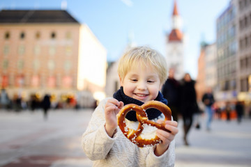 Little tourist holding traditional bavarian bread called pretzel on the town hall building background in Munich, Germany
