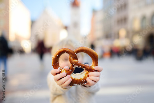 Fotografía Little tourist holding traditional bavarian pretzel in Munich