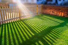 Sun Shining Through A Wooden Picket Fence Onto An Artificial Grass Lawn