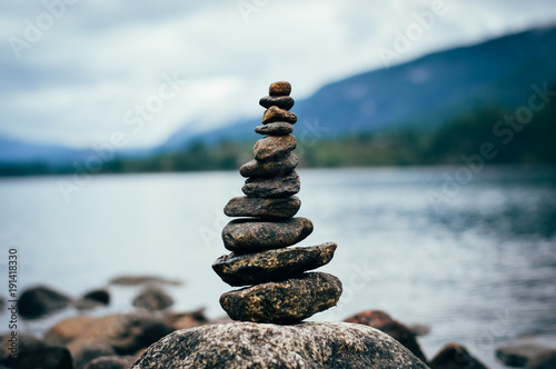 Leinwand Poster Peaceful cairn at the lake