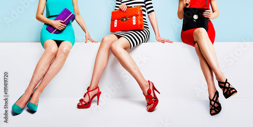 three women with beautiful shoes and bags sitting together on the bench.