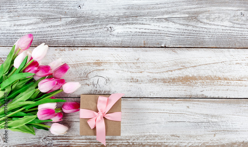 springtime pink tulips and gift box on white rustic wooden boards