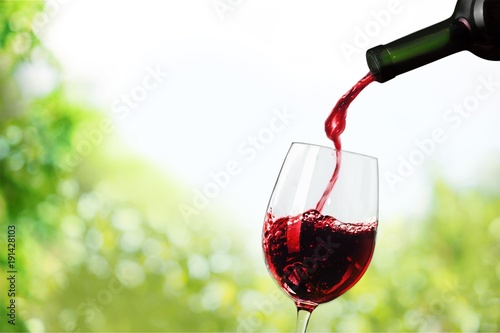 Foto Red wine pouring in glass