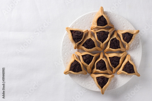 Traditional sweets for Jewish holiday of Purim. Hamantashen cookies or Aman ears, triangular cookies with poppy seeds, free space, top view