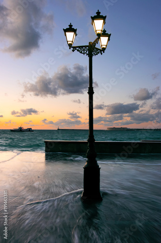 City on the water Single street lamp on wet granite seafront with flowing water at sunset. Windy stormy weather.