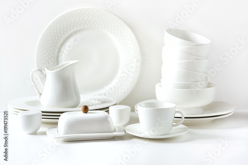 White tableware for serving. Crockery,dish, utensils and other different white stuff on white table-top. Kitchen still life. Copy space.