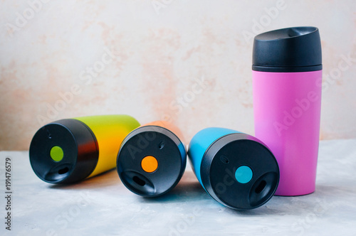 Four thermos mugs on grey background