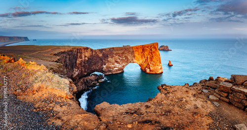 Foto auf Gartenposter See sonnenuntergang Amazing black arch of lava standing in the sea. Location cape Dyrholaey, Iceland, Europe.