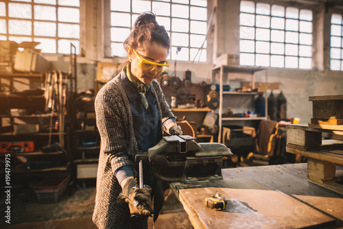 Portrait view of satisfied smiling middle aged professional female carpentry worker with steel vise on the table in the workshop Canvas Print