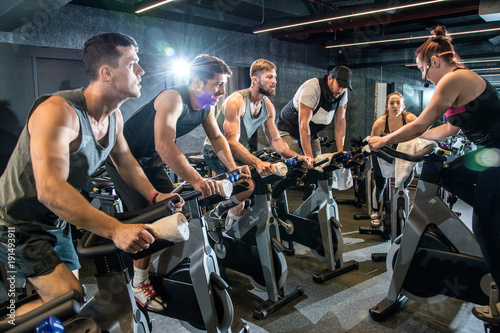 Canvas Print Group of sporty people having spinning class at gym.