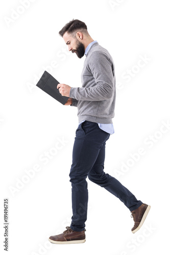 Profile view of young bearded businessman walking while reading notebook or planner. Full body length portrait isolated on white studio background.