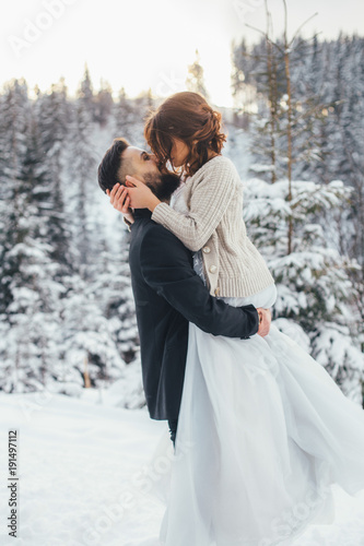 Photo Bearded man and his lovely bride pose on the snow in a magic winter forest