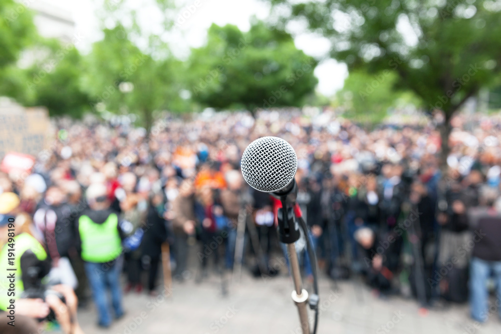 Fototapety, obrazy: Political protest. Demonstration. Microphone in focus against blurred crowd.
