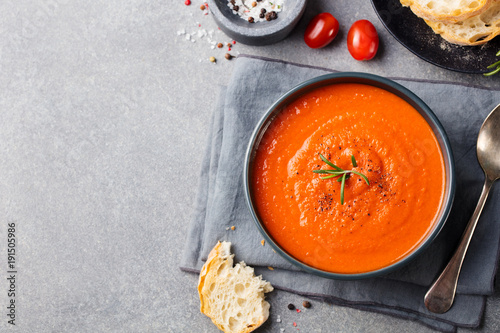 Tomato soup in a black bowl. Top view. Copy space.