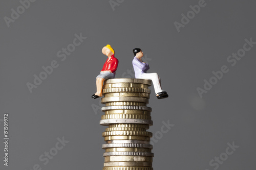 Fotografía Gender pay equality concept. man and woman on a stack of coins.