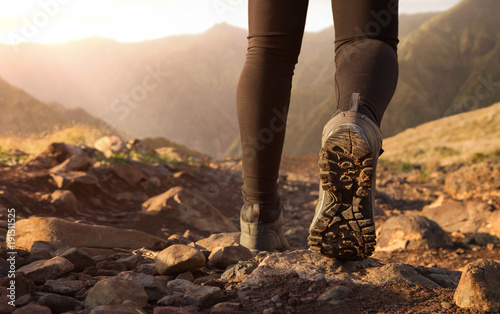 Close up of hiker boots trekking in the mountains at the sunrise with copy space