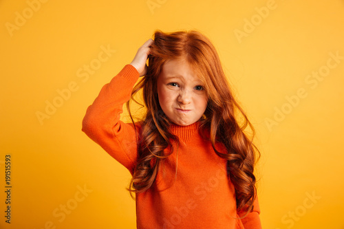 Confused little redhead girl