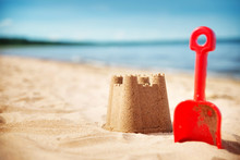 Sandcastle With A Shovel On The Sea In Summertime. Seashore On Beautiful Day. Sand On The Beach And Blue Water
