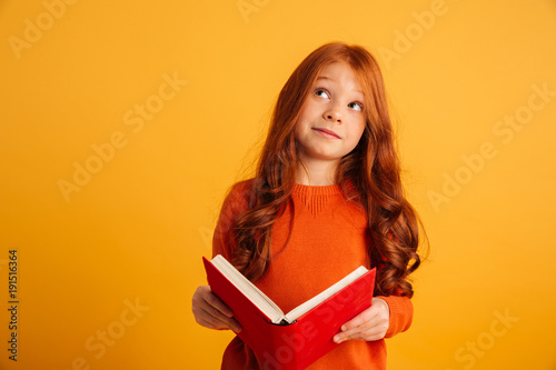 Thinking little redhead girl reading book