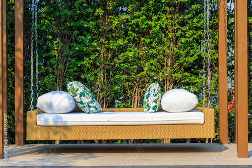 Fotografía  An outdoor resin wicker porch swing in the garden with nature background