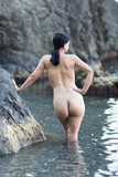 Naked dark haired woman entering in sea in cloudy day