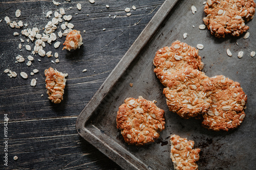 Anzac cookies on a black metal tray on wooden table with oats Fototapete