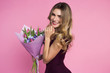 canvas print picture - Charming, pretty girl is holding a big tulip bouquet in hands.. Pink background. Happy woman's day