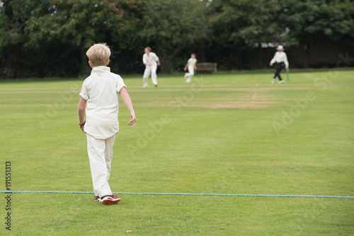 Obraz na plátně  young English school cricket player waits on the boundary with umpire in the bac