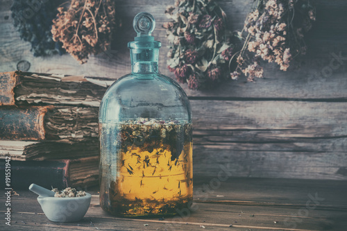 Leinwand Poster Tincture or potion bottle, old books, mortar and hanging bunches of dry healthy herbs