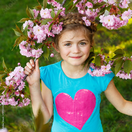 Tuinposter Kersen Pretty little girl in blossom cherry garden on beautiful spring day