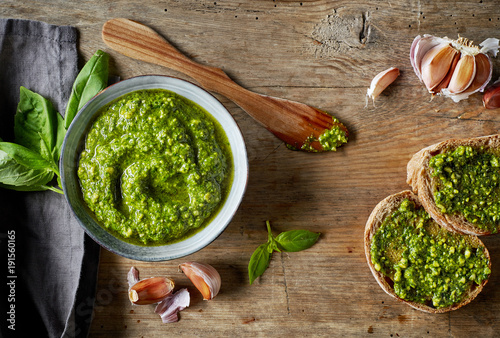 Fotografia Bowl of basil pesto on wooden table