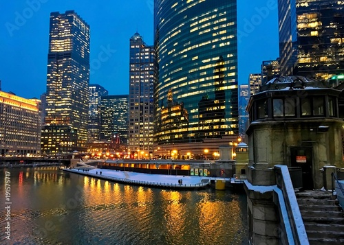 Foto op Plexiglas Chicago City night lights illuminate on a nearly frozen Chicago River as elevated train passes over snow covered Lake Street. Stairs lead to river bridgehouse.