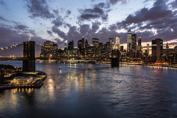 Stunning view of the nightfall over the Manhattan financial district and the Brooklyn bridge and the East river in New York city from the Manhattan bridge in the USA.