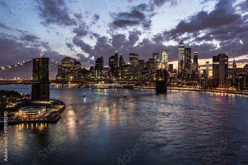 Obraz Stunning view of the nightfall over the Manhattan financial district and the Brooklyn bridge and the East river in New York city from the Manhattan bridge in the USA. - fototapety do salonu