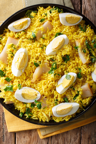 Kedgeree with smoked fish, eggs and spices close-up. Vertical top view