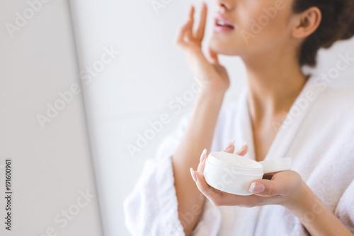 Fotografiet cropped shot of beautiful woman in bathrobe applying face cream