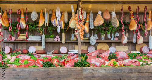 fresh food market background with raw pork and vertical assorted salami sausages.
