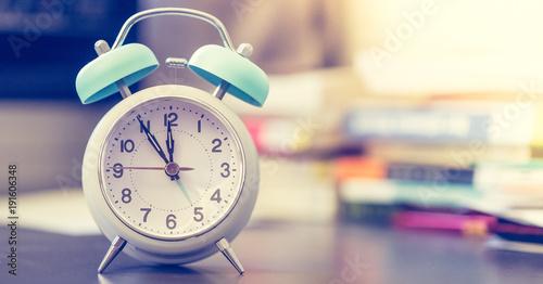 Wecker auf Schreibtisch, Bücher im Hintergrund, Breitbild Wallpaper Mural