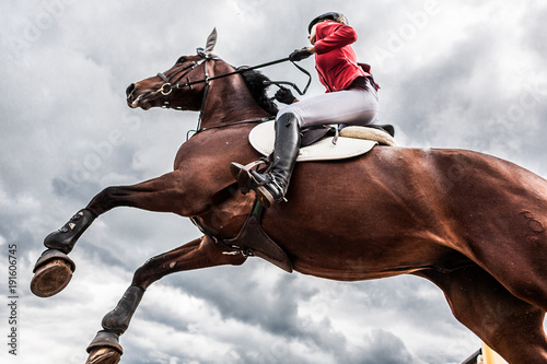 A horse with a rider jumps over an obstacle