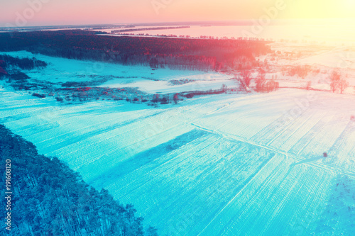 Photo Stands Turquoise Rural winter landscape. Aerial view. Field covered with snow and forest