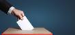 Leinwandbild Motiv Voter Holds Envelope In Hand Above Vote Ballot On Blue Background. Freedom Democracy Concept
