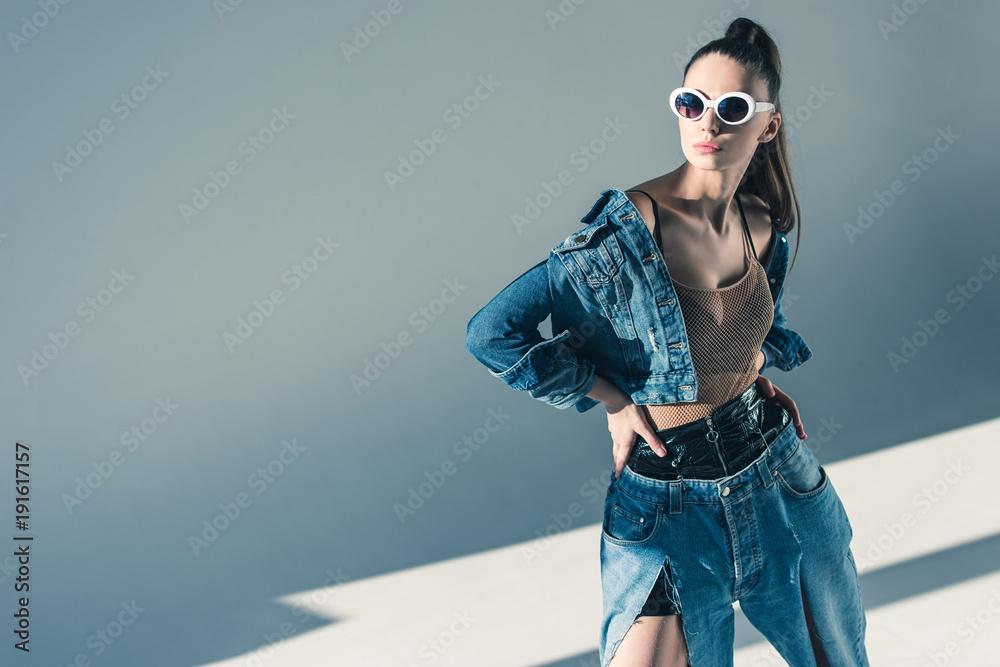 Fototapeta fashionable brunette model posing in denim style and sunglasses