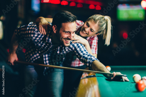 Obraz na plátně Young couple playing snooker together in bar